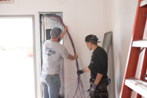 Electricians working on electrical panel and wiring
